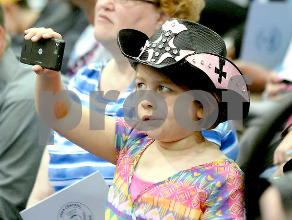 -Messenger photo by Hans Madsen<br /> <br /> Leah Lawson, of Edenton, N.C. keeps a close eye on the viewfinder of her camera phone Saturday morning as she watches for her mom, Brenda Lawson, who was graduating with from the criminal justice program at Iowa Central Community College.