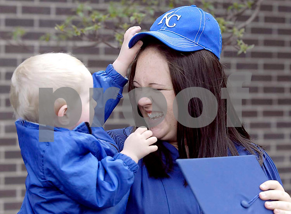 -Messenger photo by Hans Madsen<br /> <br /> Kelsey Olson, of Humboldt, finds out that her son, Riley Paulton, 2, might not be too happy with swapping caps Saturday morning following the 46th annual commencement at Iowa Central Community College. Olson graduated from the graphic technology program.