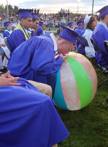 Pat George blows up one of the larger beachballs at Dracut High School graduation. (SUN/Julia Malakie)