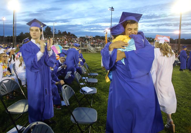 Dracut High School graduation. Daniel Law Bazarian, left, cheers as Ari Malliaros (facing) hugs his friend Pat Ghadban who was on his way up to get his diploma. (SUN/Julia Malakie)