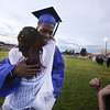 Dracut High School graduation. Freshman Keisha Dieudonne takes a break from holding a torch by the teachers' reception line, to hug her brother Erick Dieudonne. (SUN/Julia Malakie)