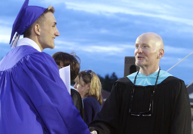 Dracut High School graduation. Steven Maxim shakes hands with superintendent Steven Stone after receiving his diploma. (SUN/Julia Malakie)