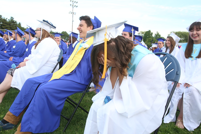 Dracut High School graduation. Brooke Birolini breaks up laughing as superintendent Steven Stone mentions her by name in reading a series of tweets @Dracutsuper that he received telling him to cancel school for snow. Stone noted that Birolini felt obliged to use all 140 characters in asking him to 'please please please please...cancel school.' At left is Bradley Bettencourt. (SUN/Julia Malakie)