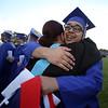Dracut High graduation. Javier Faria, who was carrying a Puerto Rican flag, hugs Spanish teacher Christine Lord, as graduates walk the perimeter of teachers. (SUN/Julia Malakie)