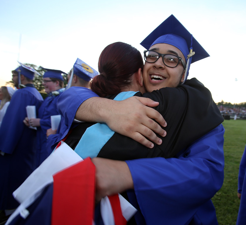 . Dracut High graduation. Javier Faria, who was carrying a Puerto Rican flag, hugs Spanish teacher Christine Lord, as graduates walk the perimeter of teachers. (SUN/Julia Malakie)
