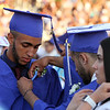 Dracut High graduation. From left, Jaeden Hylton gets help with his flower from Nemisis Lopez during speeches. At right is Natasha Jaramillo. (SUN/Julia Malakie)