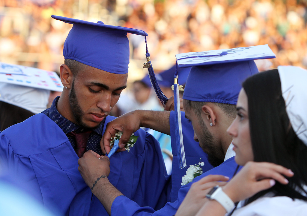 . Dracut High graduation. From left, Jaeden Hylton gets help with his flower from Nemisis Lopez during speeches. At right is Natasha Jaramillo. (SUN/Julia Malakie)