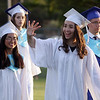 Dracut High graduation. Felicia Ros, left, and Nicole Rodriguez, waving, as graduates walk to their seats. (SUN/Julia Malakie)