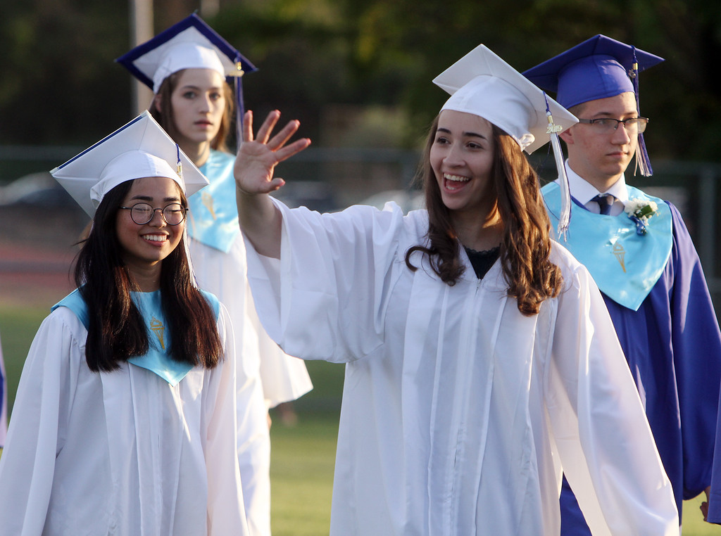 . Dracut High graduation. Felicia Ros, left, and Nicole Rodriguez, waving, as graduates walk to their seats. (SUN/Julia Malakie)