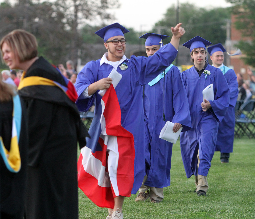 . Javier Faria carries a Puerto Rican flag at Dracut High graduation. (SUN/Julia Malakie)