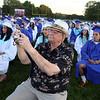 Dracut High graduation. Bob Fritsch of Nashua joins the graduates to record his granddaughter, salutatorian Megan Tyler, giving her speech. (SUN/Julia Malakie)