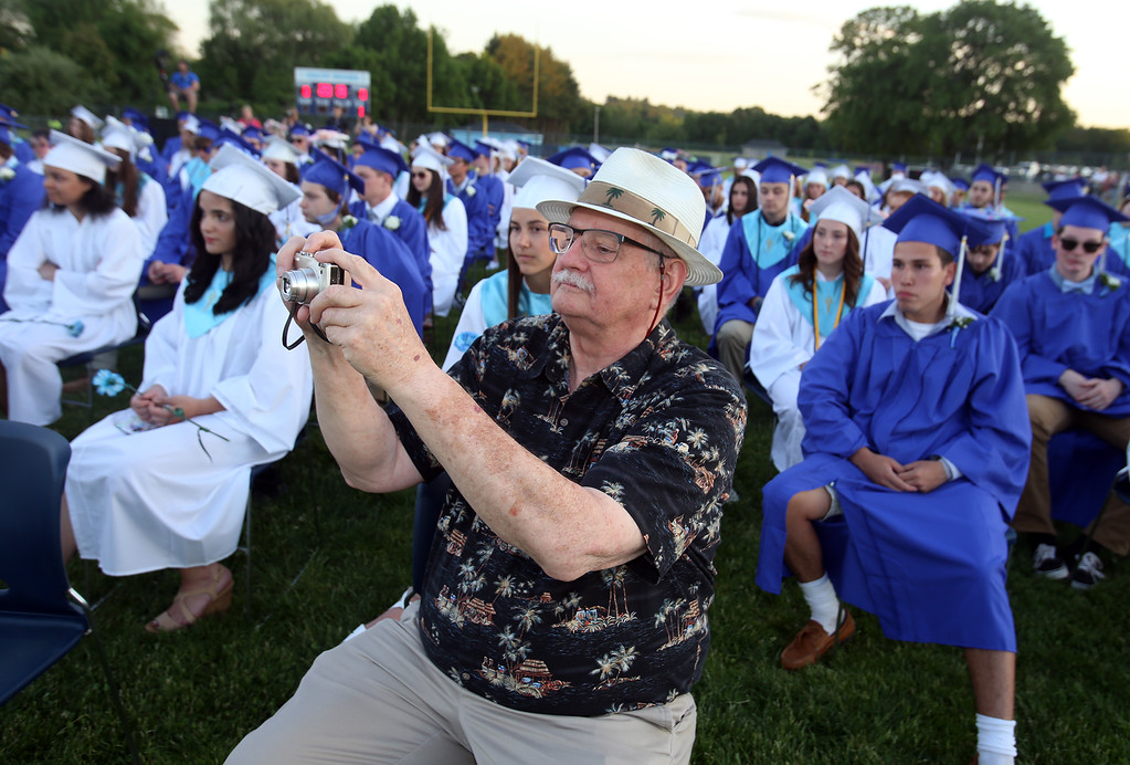 . Dracut High graduation. Bob Fritsch of Nashua joins the graduates to record his granddaughter, salutatorian Megan Tyler, giving her speech. (SUN/Julia Malakie)