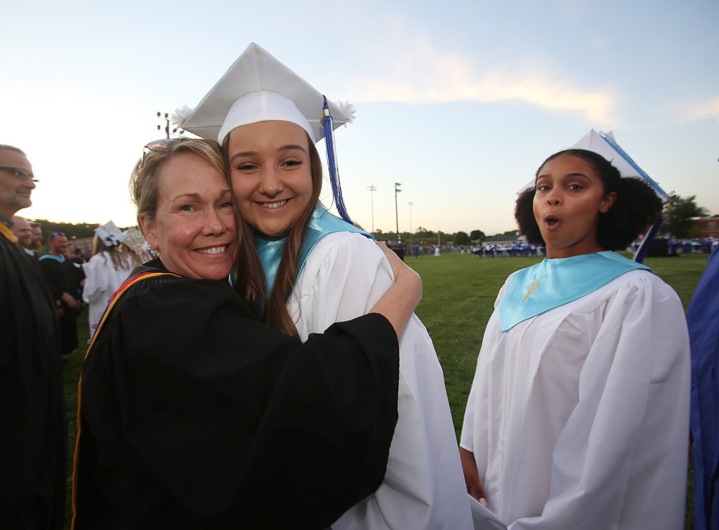 . Dracut High graduation. Kylie Germain, center, hugs financial education teacher Heather Pintal as graduates walk the perimeter of teachers. At right is Sophie Gizelis. (SUN/Julia Malakie)