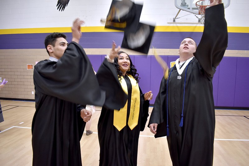 -Messenger photo by Chad Thompson<br /> <br /> Three Eagle Grove High school students practice tossing their caps prior to commencement at Robert Blue Middle School Sunday afternoon. Pictured left to right: Niko Padilla, 18, Hallie Jeske, 18, and Colton Poncin, 18.