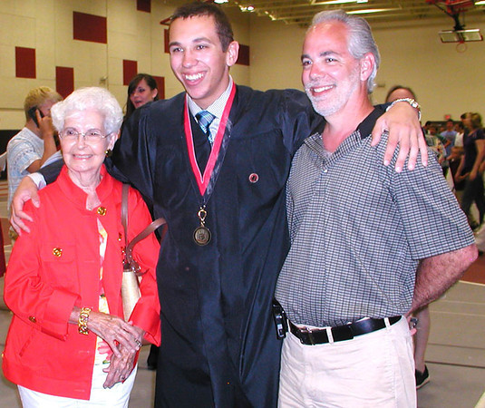 Diane Raver | The Herald-Tribune<br /> BIG FAMILY DAY: While seniors' caps and gowns were either black or red, sashes, medals and pins denoting various honors differentiated the students.