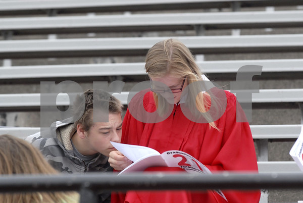 -Messenger photo by Hans Madsen<br /> <br /> About to graduate senior Mary Bethke looks for her name in the program as her boyfriend, Robert Porter, looks over her shoulder as they wait for the Fort Dodge Senior High commencement in Dodger Stadium Sunday afternoon to get started.