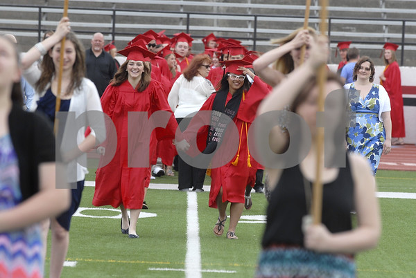 -Messenger photo by Hans Madsen<br /> <br /> Senior class president Ayenna Cagaanan, right, leads her classmates and Mackenzie Elsbecker, left, onto the field at the Fort Dodge Senior High commencement in Dodger Stadium Sunday afternoon.