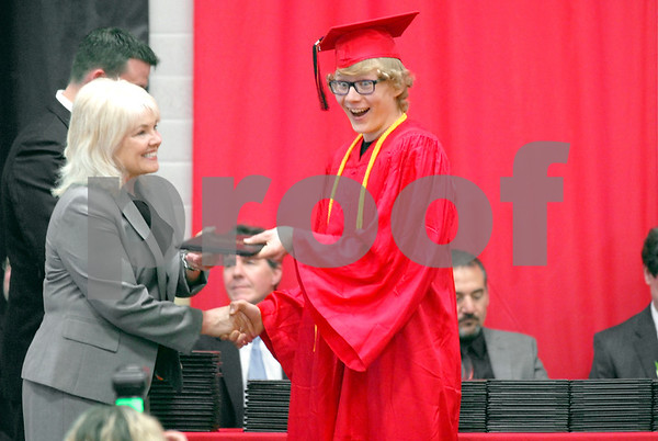 """-Messenger photo by Hans Madsen<br /> <br /> Stefan Crowl presents his best theatrical """"Surprise"""" smile Sunday afternoon as he's presented with diploma during the Fort Dodge High School commencement. School board member Deb Peterson does the honors."""