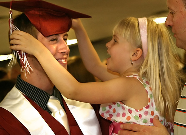 Special to the Record-Eagle/ Heather Rousseau <br /> Jared Olshove, left, laughs as his sister Kiersten fixes his graduation hat while their father, Keith, watches just after the Traverse City Christian School graduation Saturday at East Bay Calvary Church.