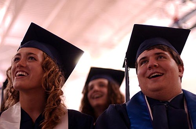 Record-Eagle/Tyler Sipe<br /> Grand Traverse Academy graduating seniors Megan Charlton, 18, and Chris Chism, 18, laugh during a slide show of classmates during Friday evening's commencement ceremony at the G.T.A. campus. Over 30 seniors graduated from the school.