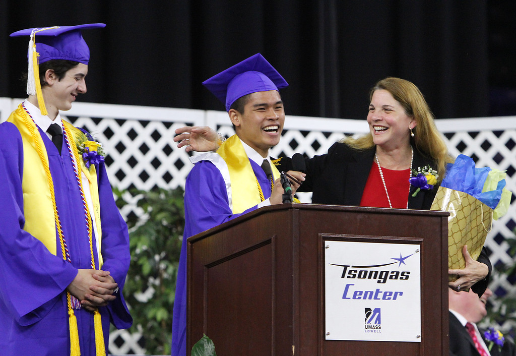 . Greater Lowell Tech graduation. Commencement speaker Roselin Acosta, Massachusetts Secretary of Labor and Workforce Development, accepts a gift from salutatorian Jaenald Javier, center, and valedictorian Rosario Puleo, asking if it included beach balls. (SUN/Julia Malakie)