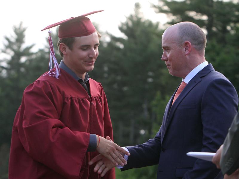 Groton-Dunstable Regional High School graduation. Timothy Colantuoni shakes hand with principal Mike Mastrullo before receiving his diploma. (SUN/Julia Malakie)
