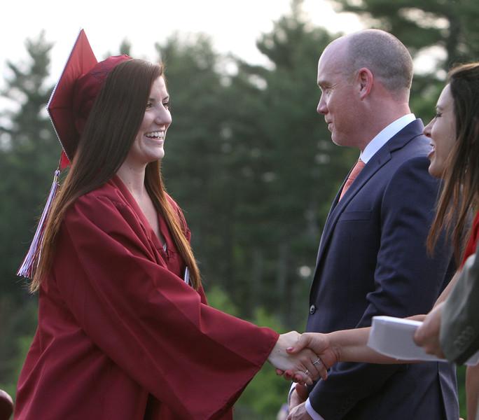 Groton-Dunstable Regional High School graduation. Shannon Cronin shakes hands with principal Mike Mastrullo and superintendent Kristan Rodriguez. (SUN/Julia Malakie)