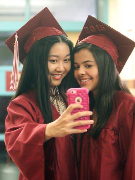 Grace Li, left, and Aline Lima, both of Dunstable, take a selfie before Groton-Dunstable Regional High School graduation. (SUN/Julia Malakie)
