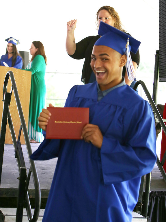 . Innovation Academy Charter School graduation. Adrik Edmonds of Tewksbury holds up his diploma. (SUN/Julia Malakie)