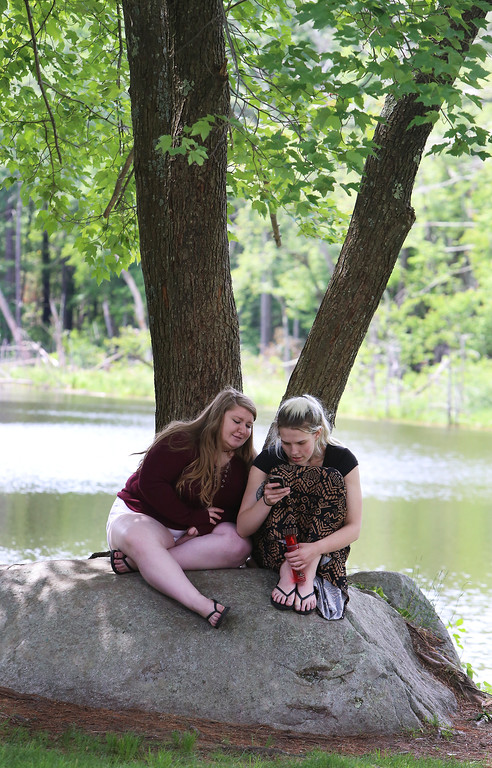 . Innovation Academy Charter School graduation. Brittany Balakin, 18, left, and McKenzie Landry, 19, both of Dracut, sit under a tree at IACS graduation. Their friend Ember True of Dracut was graduating. (SUN/Julia Malakie)