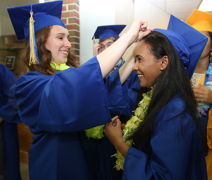 Littleton High School graduation, at the high school. Alexandra Shea, left, helps Gihanah Seb-Di Dio with her cap. (SUN/Julia Malakie)