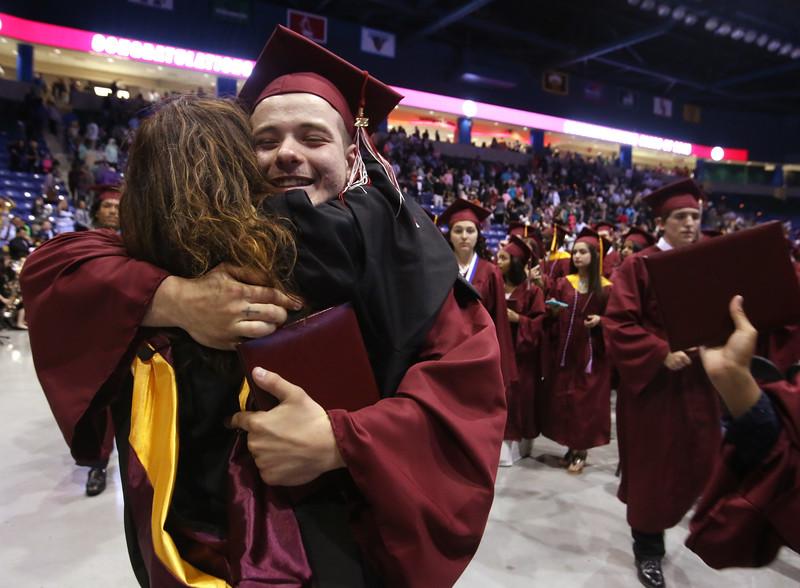Lowell High School graduation. Graduate Nathaniel Maker hugs school counselor Carla Correa as graduates leave the Tsongas Center. (SUN/Julia Malakie)