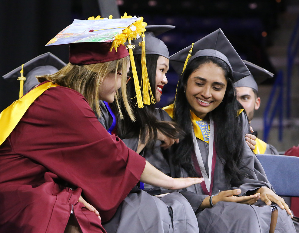 . Lowell High graduation. From left, valedictorian Emily Satterfield and salutatorian Pechthida Kim reassure Jahnvi Patel, who became emotional after receiving her Carney Medal. (SUN/Julia Malakie)