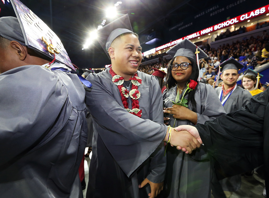 . Lowell High graduation. Capone Phouvong, center, and Lucienne Pierre, enter arena. (SUN/Julia Malakie)