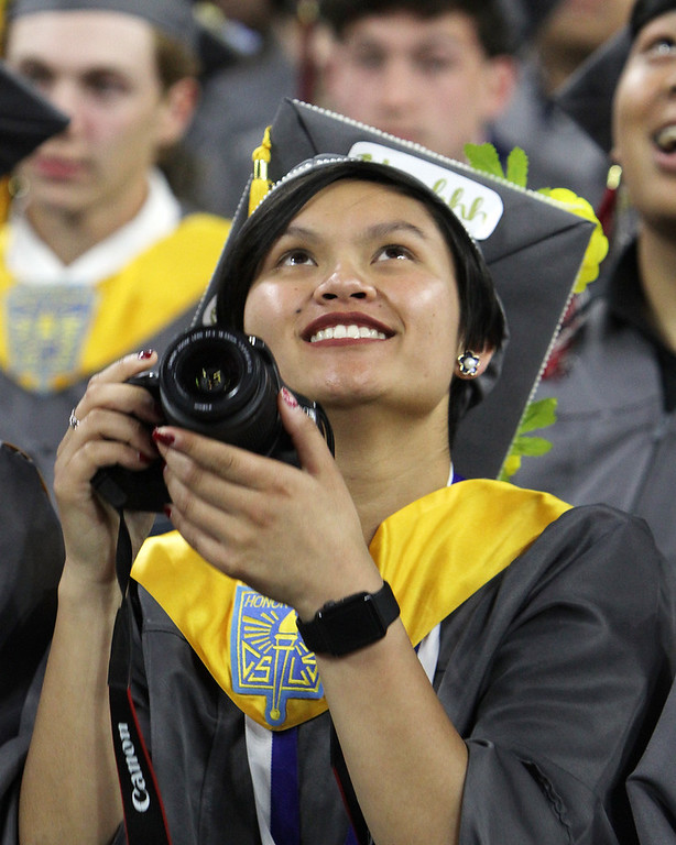 . Lowell High graduation. Sarah Boutselis with camera, watches the big screen. (SUN/Julia Malakie)