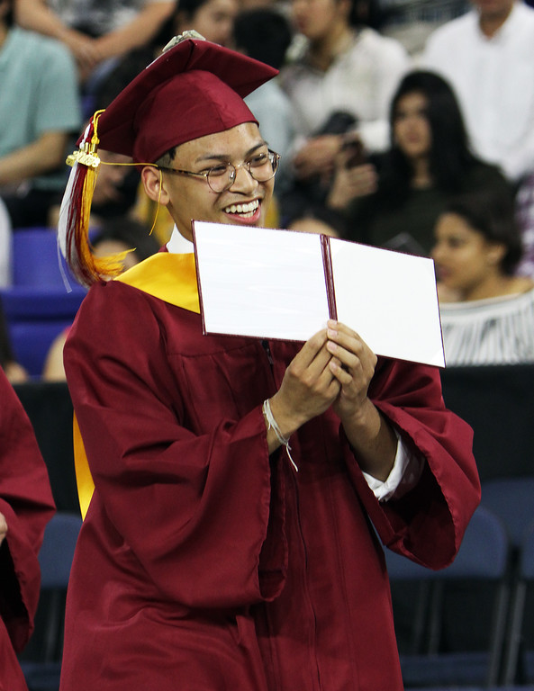 . Lowell High graduation. Peter Chea shows off his diploma case. (They were all empty.) (SUN/Julia Malakie)