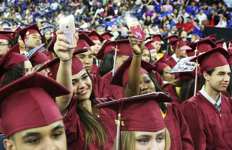 "Lowell High graduation. Manuella Porto, left, and Yaa Konamu Pokuaa, wave their phone flashlights as the Lowell High Chorus sings ""The Distance You Have Come."" (SUN/Julia Malakie)"