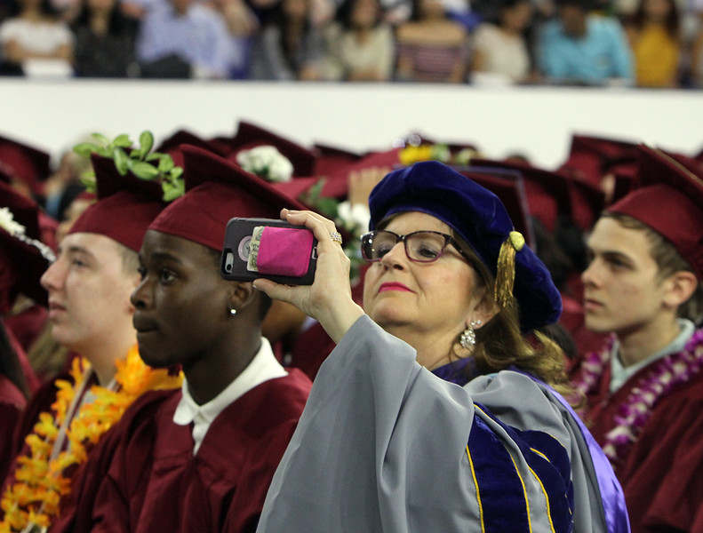 """Lowell High graduation. Fine Arts chair Dr. Sharon Clark records the LHS Show Choir singing """"Stand Up and Make A Change,"""" saying afterward, """"those are my peeps!"""" (SUN/Julia Malakie)"""