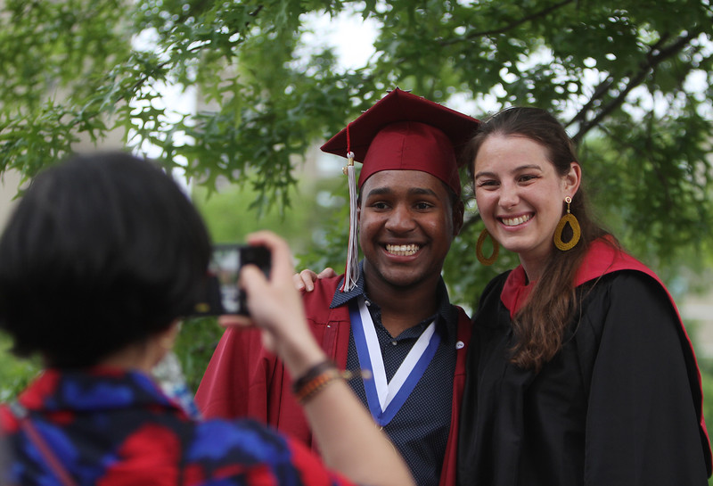 From left, teachers aide Carla Duran takes a photo of Ezequiel Nunez, and history teacher Jessica Lander before Lowell High graduation. (SUN/Julia Malakie)