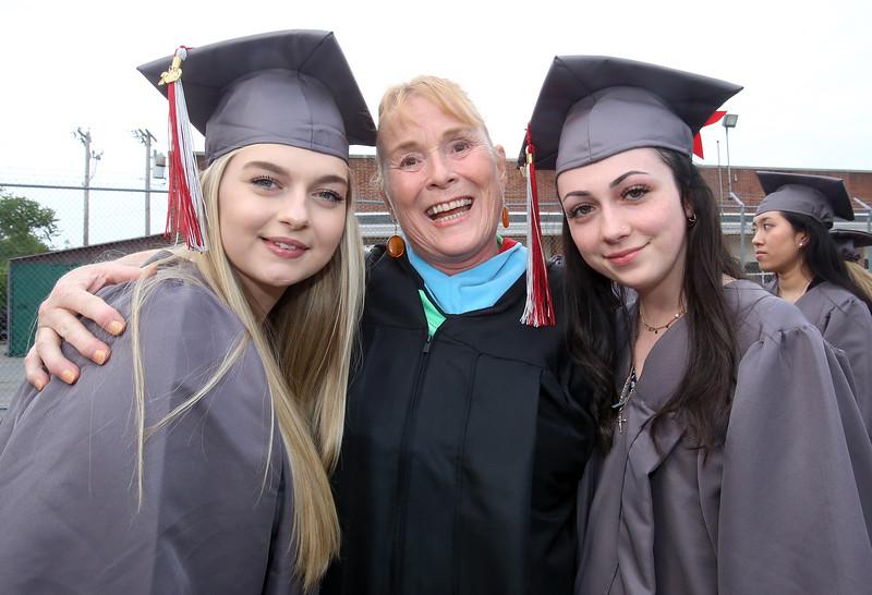 Lowell High graduation. Aliyah Jones, left, Taylor Homen, right, with homeroom teacher Ann Bienvenue. (SUN/Julia Malakie)