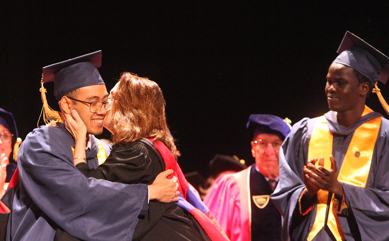 Middlesex Community College commencement. Student speakers Randy Nguyen of Woburn, getting a kiss from Pam Flaherty after his speech, and Biar Kon of Lowell. (SUN/Julia Malakie)