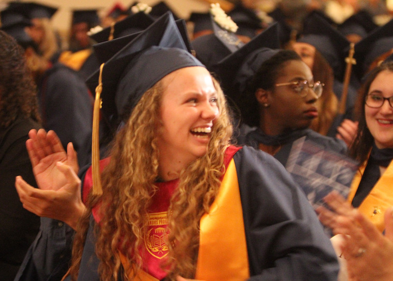 Middlesex Community College commencement. Brittany Brown of Westford, who started MCC at age 14, looks toward her brother, also a student. (SUN/Julia Malakie)