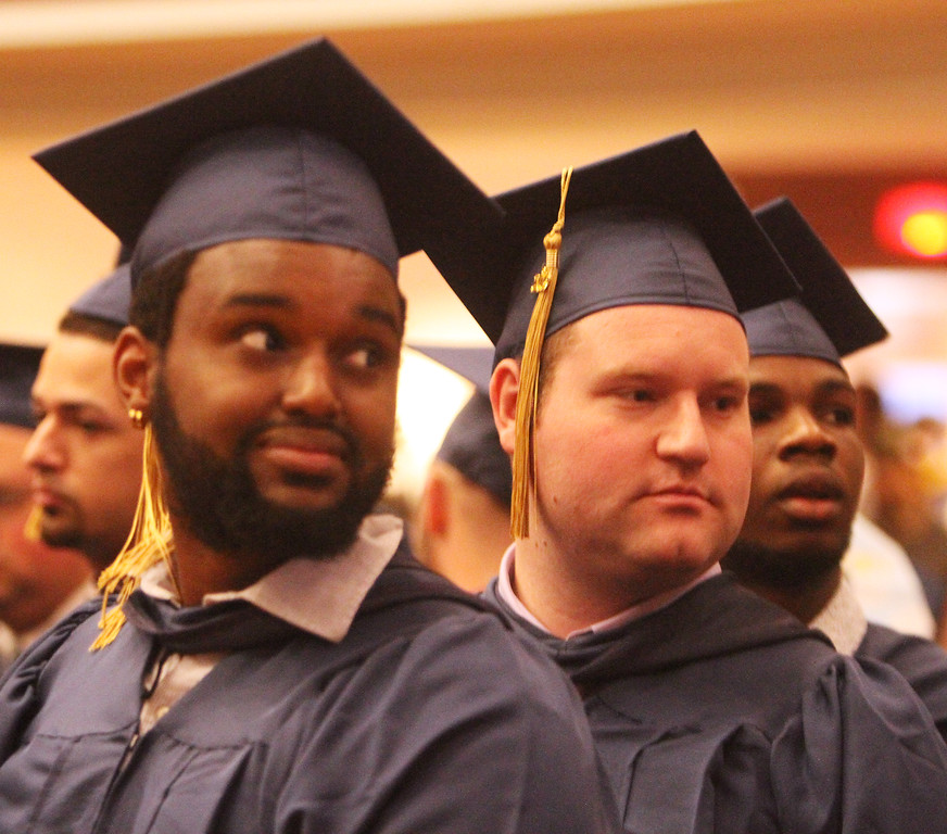 . Middlesex Community College commencement. From left, Stephen Gakuya of Lowell, Matthew Downs of Dracut, and David Ayodele of Lowell. (SUN/Julia Malakie)