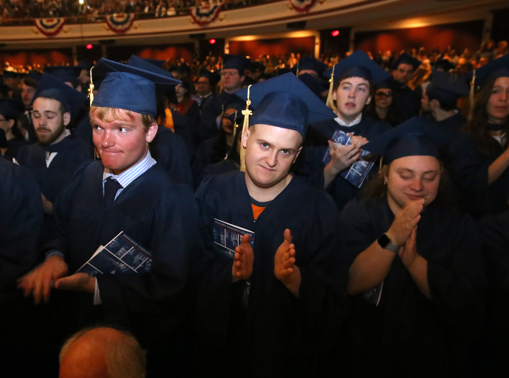 . Middlesex Community College commencement. From left Liam Melvin of Newburyport, Nicolas Pace of Stoneham and Sara Robinson of Billerica, as graduates stand to applaud faculty. (SUN/Julia Malakie)