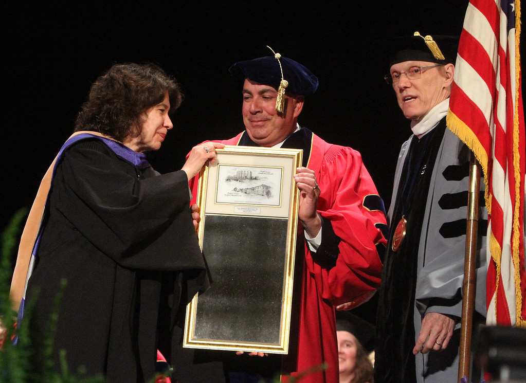 . Middlesex Community College commencement. Dean of Advancement Sherri McCormack presents mirror to commencement speaker, Bedford police chief Robert Bongiorno, as president James Mabry looks on. (SUN/Julia Malakie)