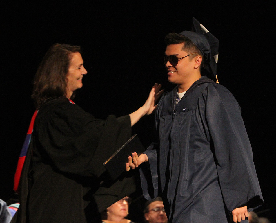 . Middlesex Community College commencement. Anh Bui of Lowell gets a pat on the shoulder from Pam Flaherty. (SUN/Julia Malakie)
