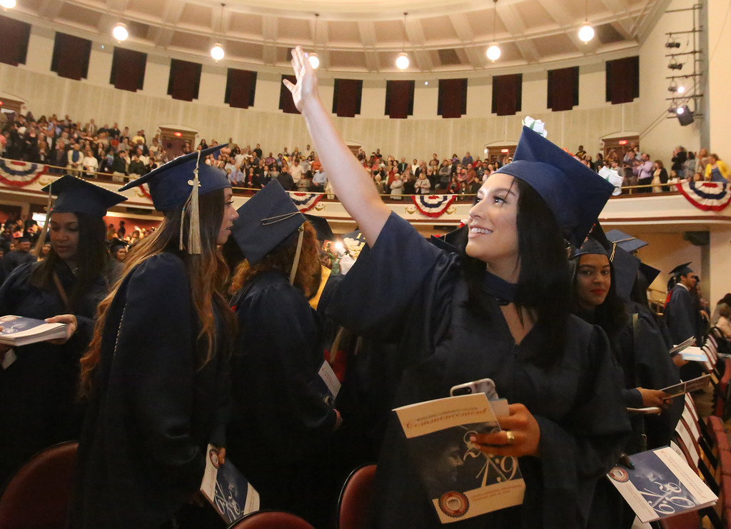 . Middlesex Community College commencement. Thania Aguirre of Haverhill waving as graduates enter. (SUN/Julia Malakie)