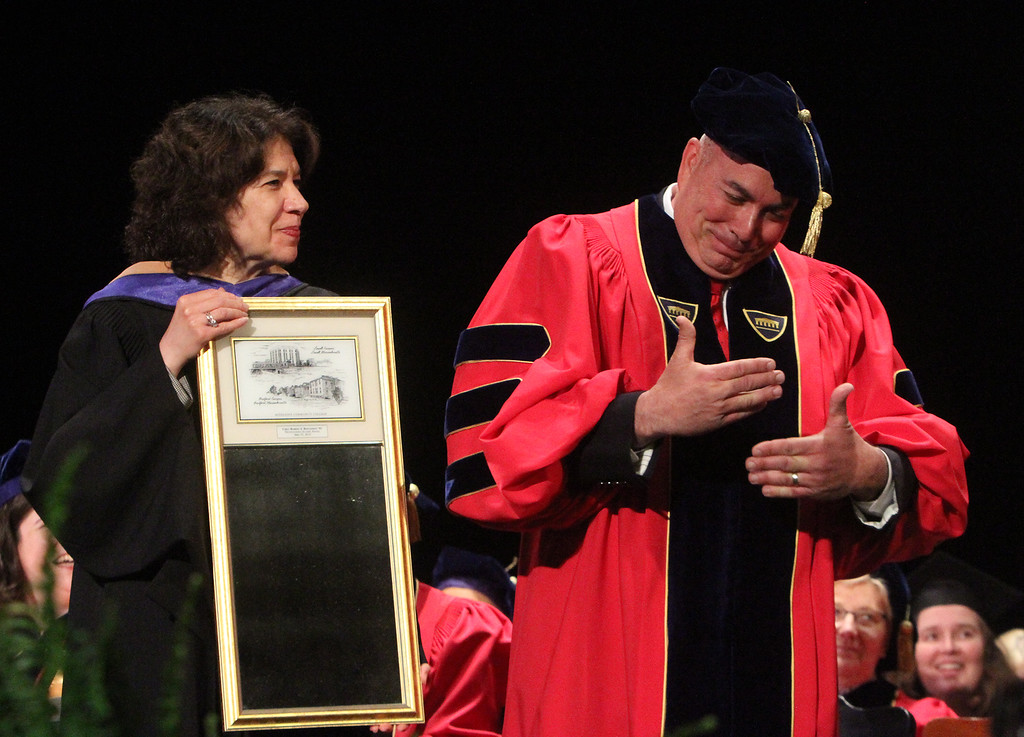 . Middlesex Community College commencement. Dean of Advancement Sherri McCormack presents mirror to commencement speaker, Bedford police chief Robert Bongiorno. (SUN/Julia Malakie)