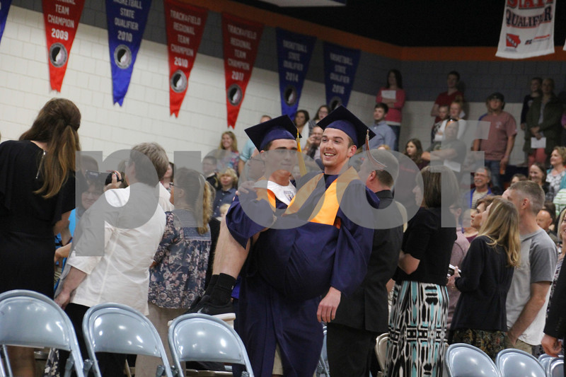 -Messenger photo by Andy Johnson<br /> <br /> Mark Condon, at left, holds up his friend Zach Walsh as they march into the commencement ceremony at Manson Northwest High School.
