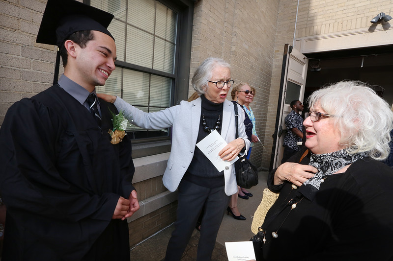 Middlesex Charter graduation at MRT. From left, graduate Elijah O'Neil of Lowell listens as his art teacher Engelie Blomerus of Lowell tells his grandmother Joanie O'Neil Lowell about him. (SUN/Julia Malakie)